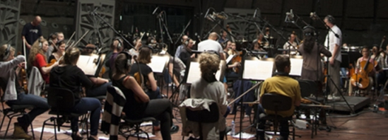 Conductor Marek Moś leading the AUKSO Alvernia Orchestra in a performance of game composer WInifred Phillips' music for the Ultimate Trailers album.