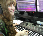 Photo of video game composer Winifred Phillips, working in her music production studio.