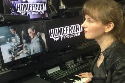 Video game music composer Winifred Phillips working in her studio on the music of the Homefront: The Revolution video game.