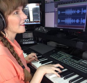 Photo of video game composer Winifred Phillips working in her music production studio.