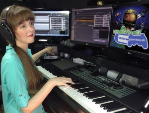 A photo of video game composer Winifred Phillips working in her music production studio on the music of LittleBigPlanet Cross Controller.