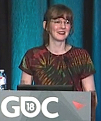 In this article for and about the craft of video game composers, Winifred Phillips is pictured in this photo from her lecture on Virtual Reality given at the popular Game Developers Conference in 2018.