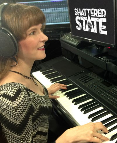 Photo of video game music composer Winifred Phillips working in her music production studio on the musical score of the Shattered State VR game from Supermassive Games.