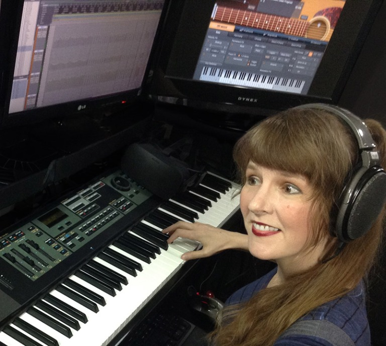In this article about Virtual Presence in VR written for video game composers, Winifred Phillips (video game composer) is here pictured working in her music production studio.