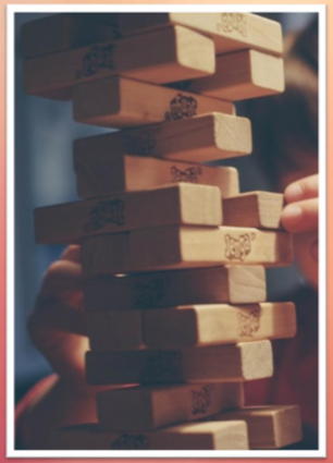 A depiction of the game of Jenga, used as a visual metaphor representing the vertical layering music composition technique (as described in video game composer Winifred Phillips' article).