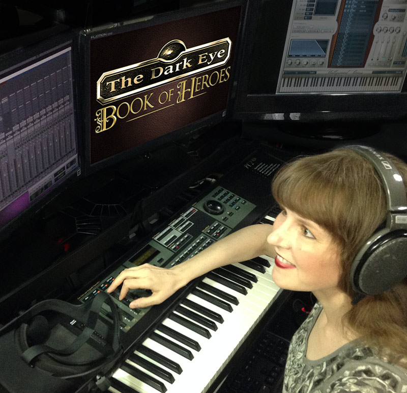 This photo includes game music composer Winifred Phillips working in her production studio. Phillips is the game music composer for The Dark Eye: Book of Heroes game, developed by Random Potion for Wild River Games. Her credits include titles from 5 of the most well-known game franchises, and she is one of the foremost authorities on video game music, having presented lectures at the Game Developers Conference (GDC), the Library of Congress in Washington DC, and the Society of Composers and Lyricists in NYC.