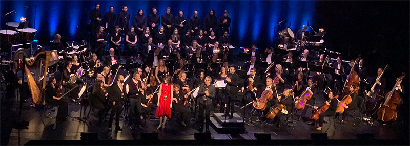Photo taken during the standing ovation at the end of the Montreal performance of the Assassin's Creed Symphony in 2019, in which composer Winifred Phillips took the stage in connection with her video game music for Assassin's Creed Liberation, featured in the Assassin's Creed Symphony world tour.