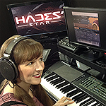 Photo of video game music composer Winifred Phillips, working in her music studio on the score to the Hades' Star video game.