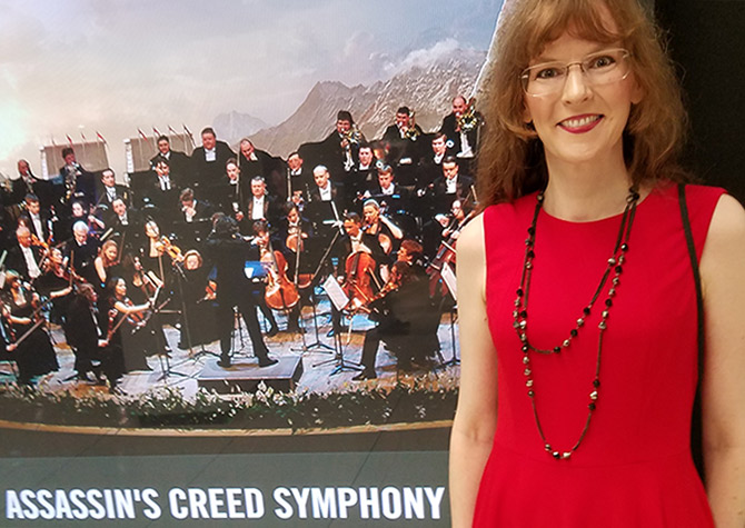 Photo of video game composer Winifred Phillips, pictured standing in front of the official poster for the Assassin's Creed Symphony concert tour.